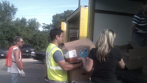 Daniel loading up a donation of food for a family waiting in their car. The donation includes dry staples, vegetables, meat, bread, and a pastry
