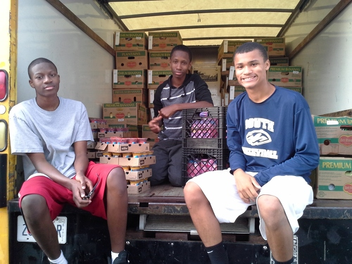 Martin, David and friend loading produce into truck for distribution