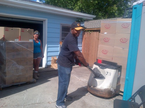 Marilyn looks on as Theo maneuvers a pallet of food with our donated pallet jack